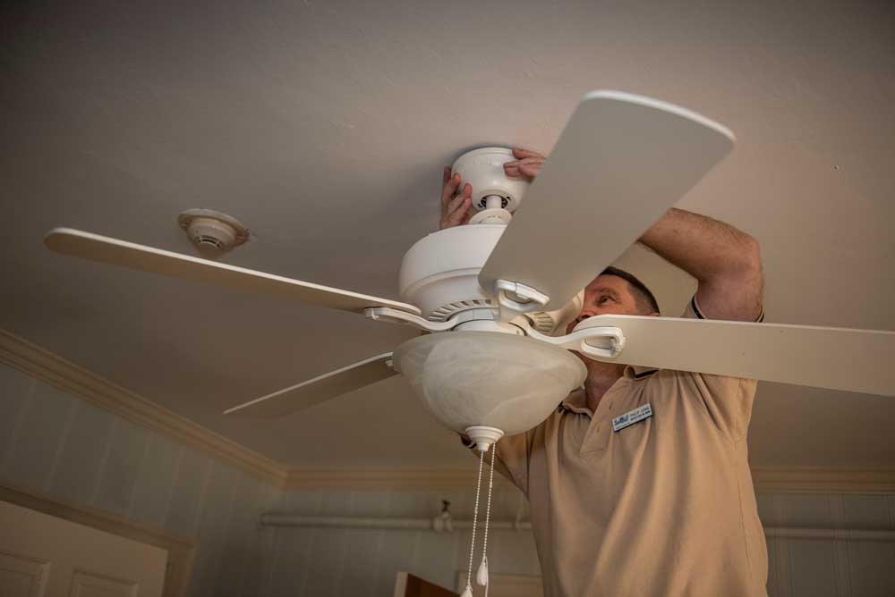 Maintenance repairs a light fixture
